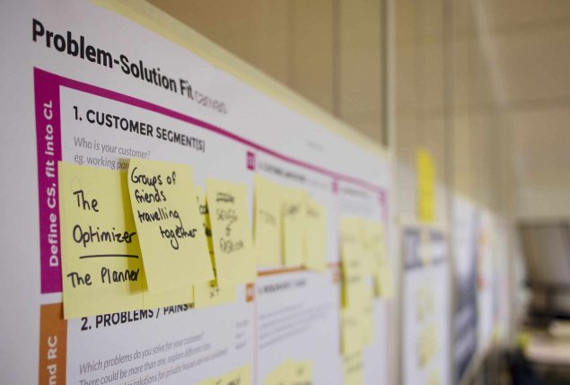 Brainstorming ideas by placing sticky notes on a white board during an Employee Assistance Program conference.