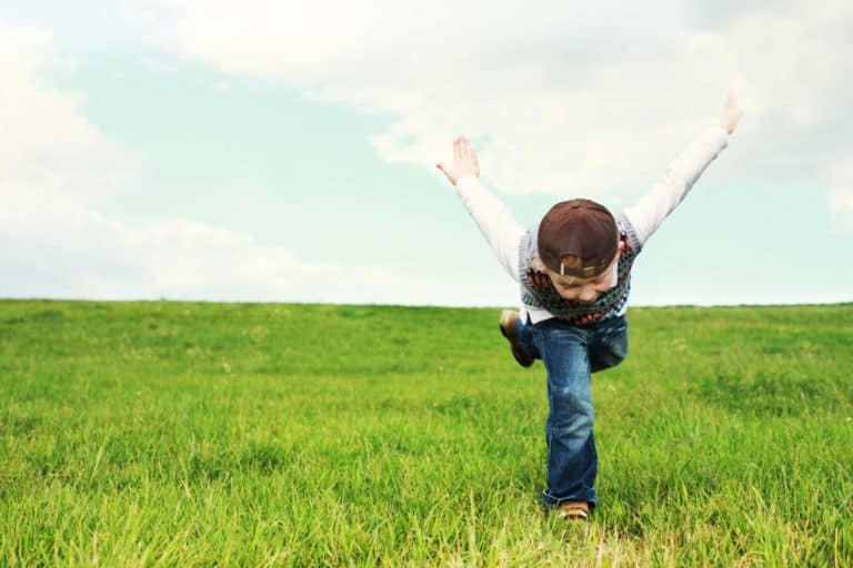 An energetic child running in a field.